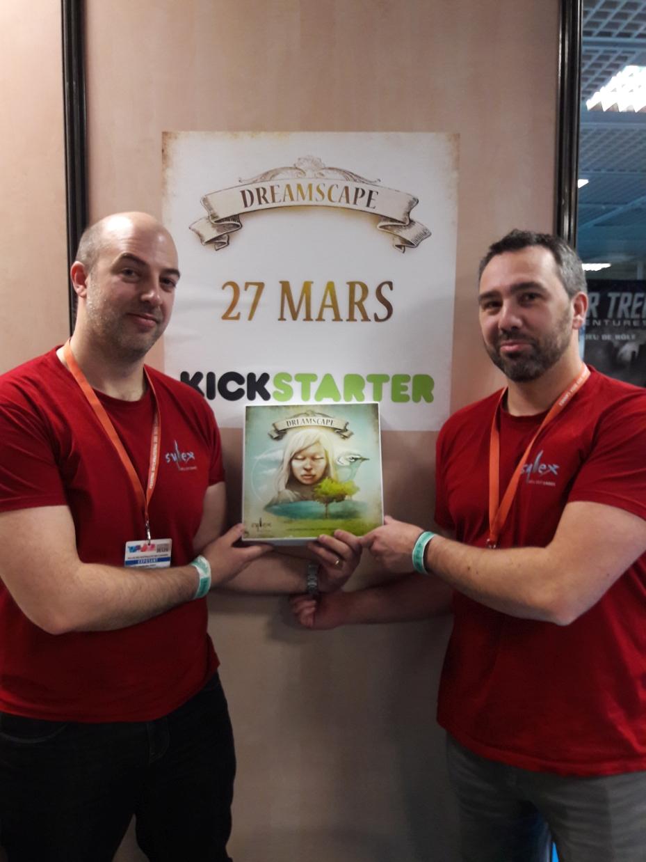 Pierre et Florian tenant une boîte prototype de Dreamscape devant l'affiche annonçant la campagne Kickstarter le 27 mars